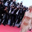 """Michèle Laroque dans sa robe rebrodée de sequins dorés signée Zuhair Muraid et avec ses bijoux, une bague et des boucles d'oreilles Montblanc Princesse Grace de Monaco Pétale entrelacés en or rose et diamants - Montée des marches du film """"Dragon 2"""" lors du 67e Festival du film de Cannes le 16 mai 2014."""