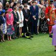 La reine Elizabeth II en arrêt devant un chien invité le 21 mai 2014 dans le parc de Buckingham Palace pour la première garden party de l'année.