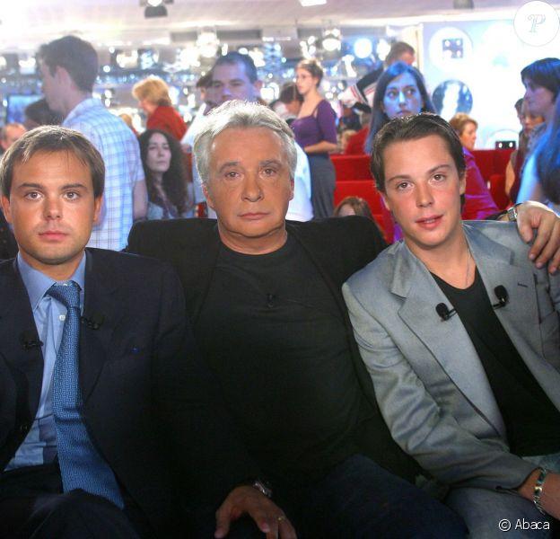 """Michel Sardou entouré de ses fils Romain et Davy sur le plateau de """"Vivement Dimanche"""", septembre 2002."""