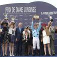"""Kate Winslet, aux côtés de Bertrand Bélinguier, remet le prix principal au jockey Gregory Benoist lors du 165e """"Prix de Diane Longines"""" à l'hippodrome de Chantilly le 15 juin 2014."""