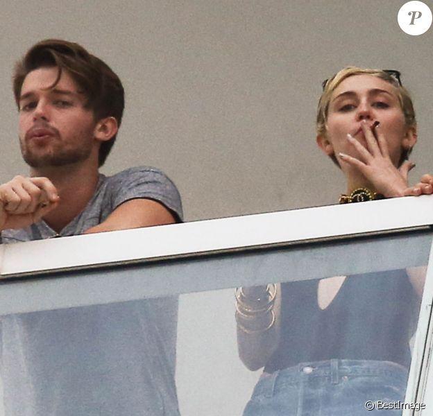 Exclusif - Miley Cyrus et son petit ami Patrick Schwarzenegger fument une drôle de cigarette au balcon de leur chambre d'hôtel à Miami, le 4 décembre 2014
