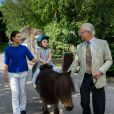 La princesse Estelle de Suède fait un tour à dos de poney avec sa mère la princesse Victoria et son grand-père le roi Carl XVI Gustaf de Suède, à Skansen en juillet 2014.