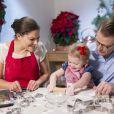 La princesse Estelle de Suède en plein atelier gâteaux de Noël avec ses parents la princesse Victoria et le prince Daniel en décembre 2013