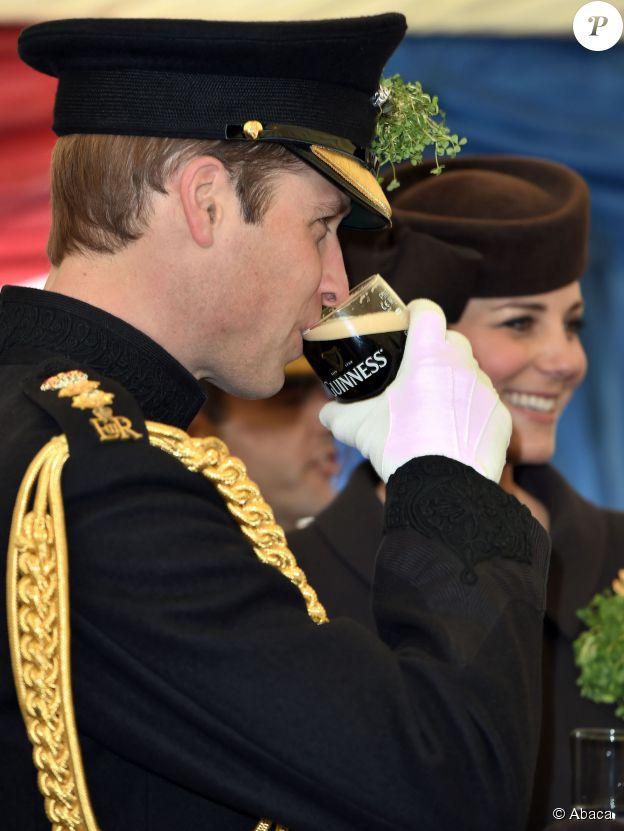 Le prince William boit une Guinness devant son épouse Kate Middleton le 17 mars 2015 à la base des Irish Guards lors de la Saint Patrick.