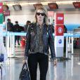 Rosie Huntington-Whiteley à l'aéroport JFK à New York, porte un perfecto, une chemise et des bottines Saint Laurent, un jean noir Paige et un sac Givenchy (modèle Lucrezia). Le 3 mai 2015.