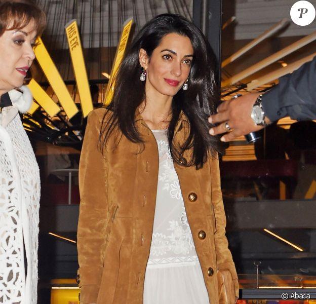 Amal Clooney quitte le Public Theater avec sa mère Baria Alamuddin, habillée d'un manteau Gucci, d'une robe Alberta Ferretti et de sandales blanches. Le 1er mai 2015.