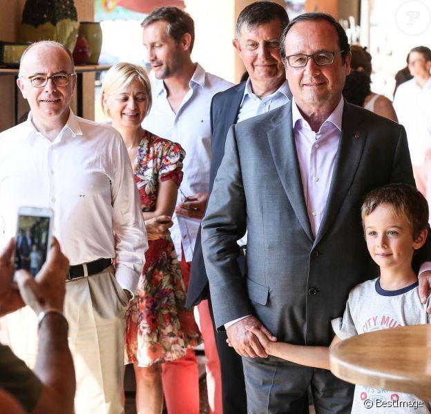 Exclusif - François Hollande et Bernard Cazeneuve se promènent dans le village de Aiguines (dans le Var) où le premier a fêté ses 61 ans et assisté au mariage de son ministre de l'intérieur, le 12 août 2015. Un remariage, avec Véronique que l'on peut voir en arrière-plan en robe fleurie, dans le plus grand secret dont on apprend à peine l'existence.