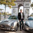 """Denis Brogniart pose devant l'Aston Martin DB10 à Paris le 10 octobre 2015 à l'occasion de la sortie du nouveau James Bond, """"Spectre"""" qui sortira le 11 novembre."""