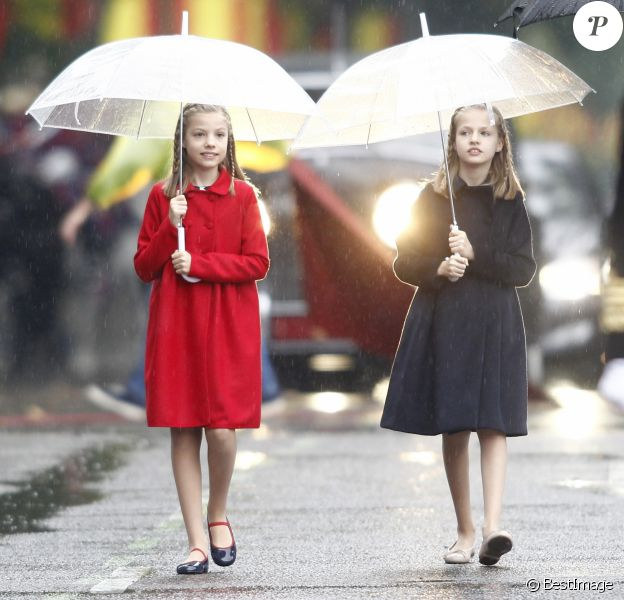 L'infante Sofia d'Espagne (en manteau rouge) et la princesse Leonor des Asturies (en manteau bleu), filles du roi Felipe VI et de la reine Letizia, ont bravé la pluie à Madrid le 12 octobre 2016 lors des célébrations de la Fête nationale.