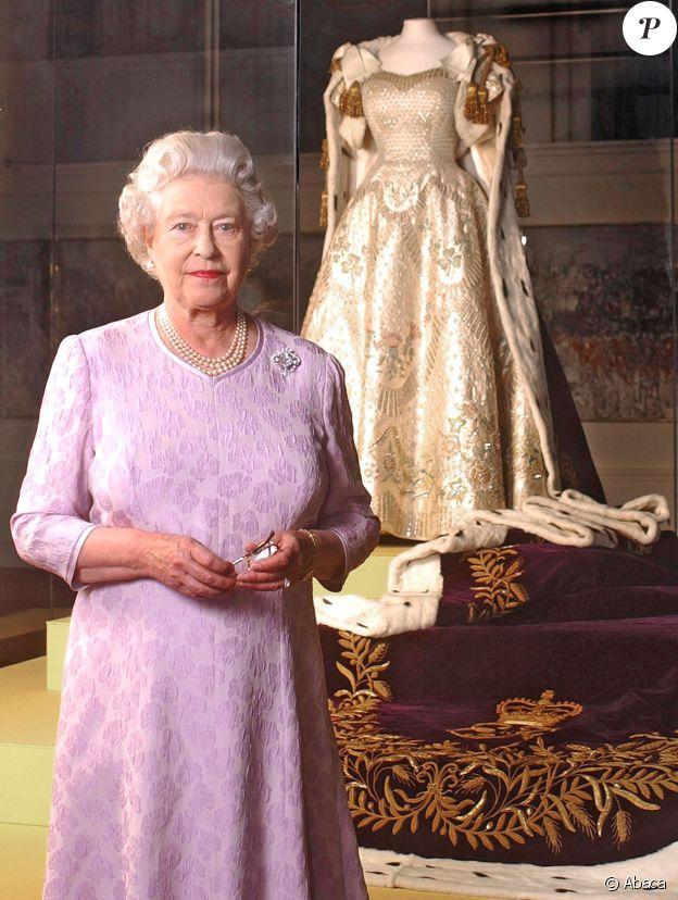 La reine Elisabeth II pose devant la robe de son courronement dans le cadre d'une exposition d'été à Buckingham Palace, le 1er août 2003.