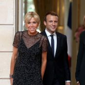 Brigitte Macron, en robe noire et brillante, main dans la main avec Emmanuel