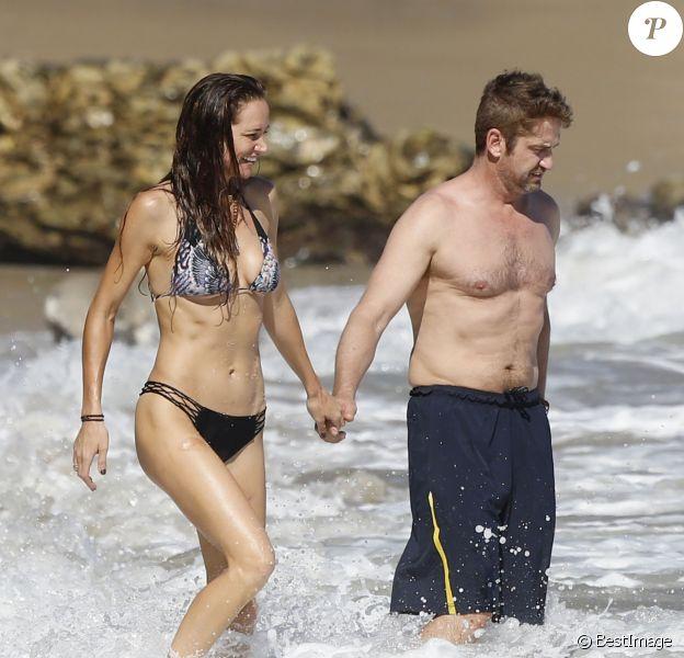 Gerard Butler et sa compagne Morgan Brown s'embrassent sur la plage de Malibu le 12 octobre 2015.