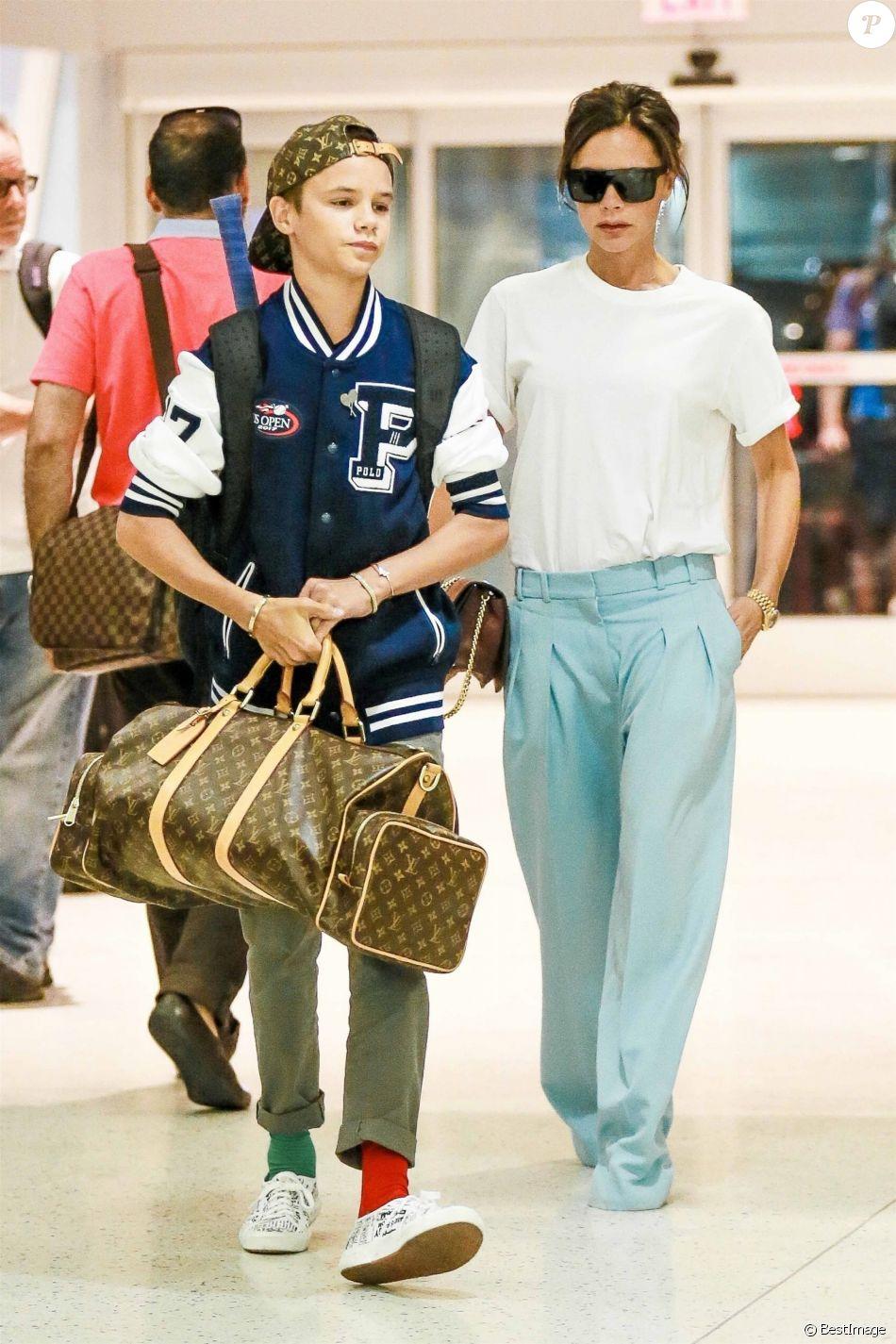 Victoria Beckham et son fils Romeo (habillé d'une casquette Louis Vuitton x Supreme, d'une veste Polo Ralph Lauren, chaussé de baskets Comme des Garçons et tenant un sac Louis Vuitton) à l'aéroport de JFK à New York. Le 30 août 2017.