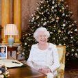 La reine Elizabeth II dans le salon 1844 au palais de Buckingham pour l'enregistrement de son allocution de Noël, le 25 décembre 2017. Sur le bureau à côté d'elle, des photos de George et Charlotte de Cambridge, de son mariage avec le prince Philip et de leurs noces de platine. Mais dans la pièce figurait aussi une photo des fiançailles du prince Harry et de Meghan Markle, qui s'apprête à entrer dans la famille.
