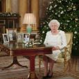 Allocution de Noël de la reine Elizabeth II depuis le salon 1844 au palais de Buckingham, le 25 décembre 2017. Sur le bureau à côté d'elle, des photos de George et Charlotte de Cambridge, de son mariage avec le prince Philip et de leurs noces de platine. Mais dans la pièce figurait aussi une photo des fiançailles du prince Harry et de Meghan Markle, qui s'apprête à entrer dans la famille.