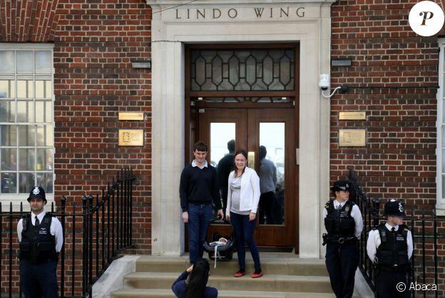 Un couple de jeunes parents avec son bébé pose sur le perron de l'aile Lindo de l'hôpital St Mary à Londres le 23 avril 2018 alors que les médias guettent la duchesse de Cambridge...