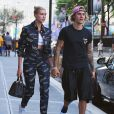 Hailey Baldwin et Justin Bieber se tiennent la main en sortant du restaurant Nobu à Los Angeles. Hailey porte un ensemble Versace, le 5 juillet 2018.  Justin Bieber and Hailey Baldwin are spotted holding hands outside of Nobu restaurant in New York City following a dinner date. Bieber, 24, went casual in a black T-shirt and matching athletic shorts, white slippers and a purple backwards baseball cap. Baldwin, 21, sported a matching denim Versace jacket and pants with a white crop top underneath. She paired the look with casual white sneakers and a purse. 5th july 2018.05/07/2018 - Los Angeles