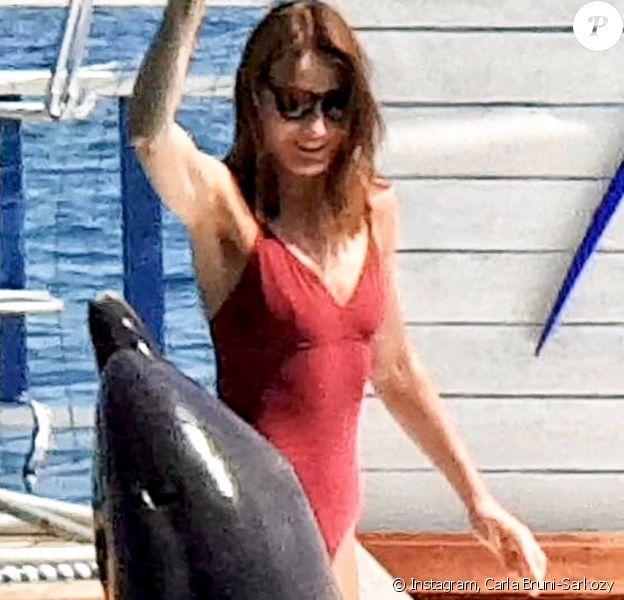 """Carla Bruni-Sarkozy pose en maillot rouge façon """"Alerte à Malibu"""" lors de ses vacances, Instagram le 26 juillet 2019."""