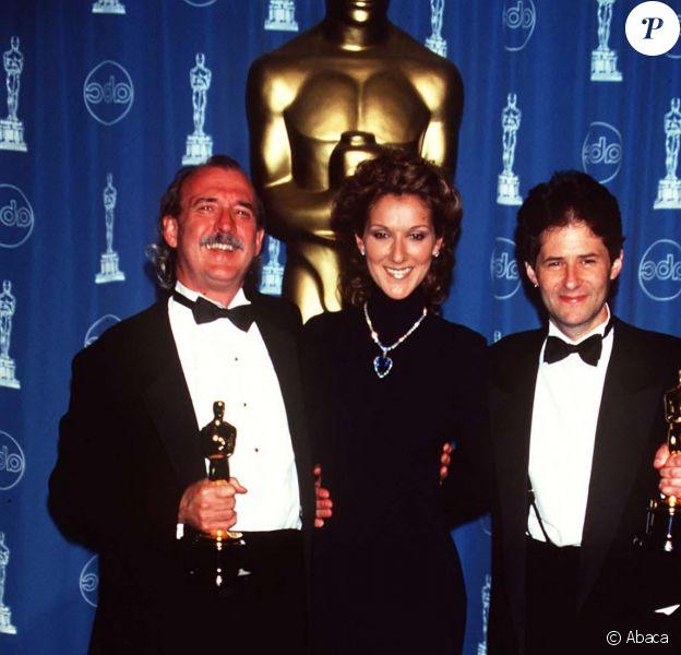 Céline Dion pose avec Will Jennings et James Horner à la 70e cérémonie des Oscars en 1998 à Los Angeles