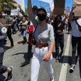 """Emily Ratajkowski manifeste avec le mouvement Black Lives Matter contre les violences policières suite à la mort de George Floyd. Elle porte un carton sur lequel est inscrit : """"Démantelez les structures de pouvoir de l'oppression"""". Los Angeles, le 30 mai 2020."""