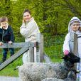 La princesse Victoria de Suède, le prince Oscar et la princesse Estelle visitent un enclos de moutons et les caressent au château de Haga à Solna le 18 mai 2020.
