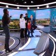 Jean-Pierre Pernaut avec ses enfants Tom et Lou, sa femme Nathalie Marquay et son petit-fils Léo sur le plateau du JT de 13h de TF1, le 18 décembre 2020