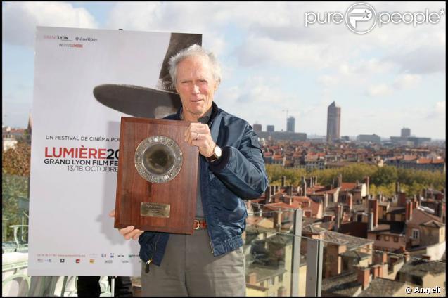 Clint Eastwood pose avec son prix devant l'affiche de la manifestation, à l'occasion de la clôture du Festival Lumière de Lyon, le 18 octobre 2009 !