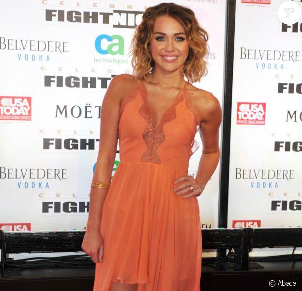 Miley Cyrus, superbe dans une robe orange décolletée et fendue, a fait forte impression au côté de son fiancé Liam Hemsworth lors de la soirée Celebrity Fight Night de Mohamed Ali, le 24 mars 2012 à Phoenix.
