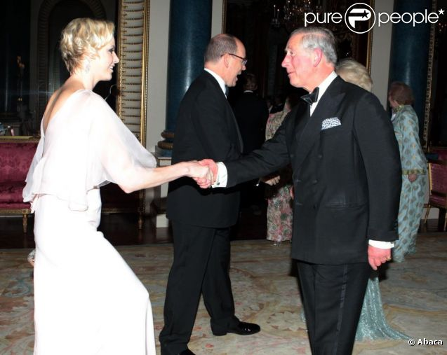 Charlene de Monaco, magnifique en robe Dior, fait la révérence devant le prince Charles, tandis que le prince Albert salue la duchesse Camilla.   Le prince Charles et Camilla Parker Bowles donnaient le 18 mai 2012 à Buckingham Palace un dîner pour de nombreux royaux étrangers, invités en l'honneur du jubilé de diamant de la reine Elizabeth II. Les convives avaient plus tôt dans la journée déjeuné avec la monarque au château de Windsor.