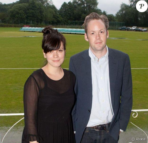 Lily Allen et son époux Sam Cooper à l'inauguration d'un club de cricket près de Londres le 8 juillet 2012. La chanteuse porte une robe noire et affiche quelques rondeurs.