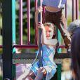 Suri Cruise, une enfant comme les autres qui s'amuse dans un parc de Brooklyn, à New York le 24 septembre 2012, sous le regard de sa maman Katie Holmes