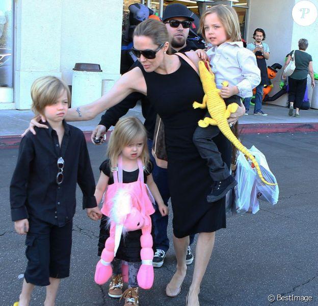 Angelina Jolie emmène trois de ses enfants faire du shopping pour Halloween le 28 octobre 2012 à Sherman Oaks en Californie dans le magasin Party City : elle porte dans ses bras son fils Knox, tandis que Shiloh, l'aînée, tient la main de la petite Vivienne