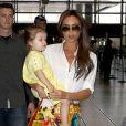 Victoria Beckham, ultrachic en chemise blanche, minijupe Carven (collection automne-hiver 2012) et sandales Chloé à l'aéroport de Los Angeles avec sa fille Harper. Le 1er juin 2013.