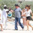 Sylvester Stallone, saluant un vendeur de chapeau, avec sa femme Jennifer Flavin arrivant au club 55 à Saint-Tropez le 4 août 2013