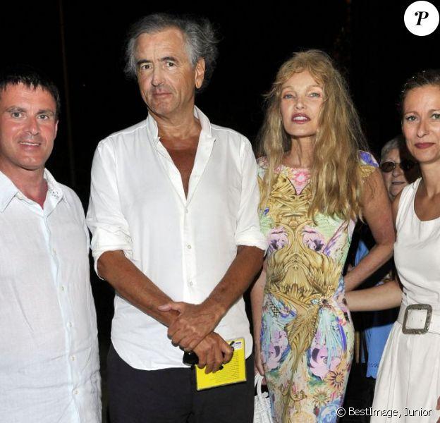 Le ministre de l'Intérieur, Manuel Valls, le philosophe Bernard-Henri Lévy et sa femme l'actrice Arielle Dombasle, et Anne Gravoin, l'épouse du ministre, posent pour une photo souvenir apres le concert du 'Travelling Quartet' d'Anne Gravoin, dans le cadre du Off du 64eme Festival de Musique de Menton, dans le sud de la France le 5 août 2013