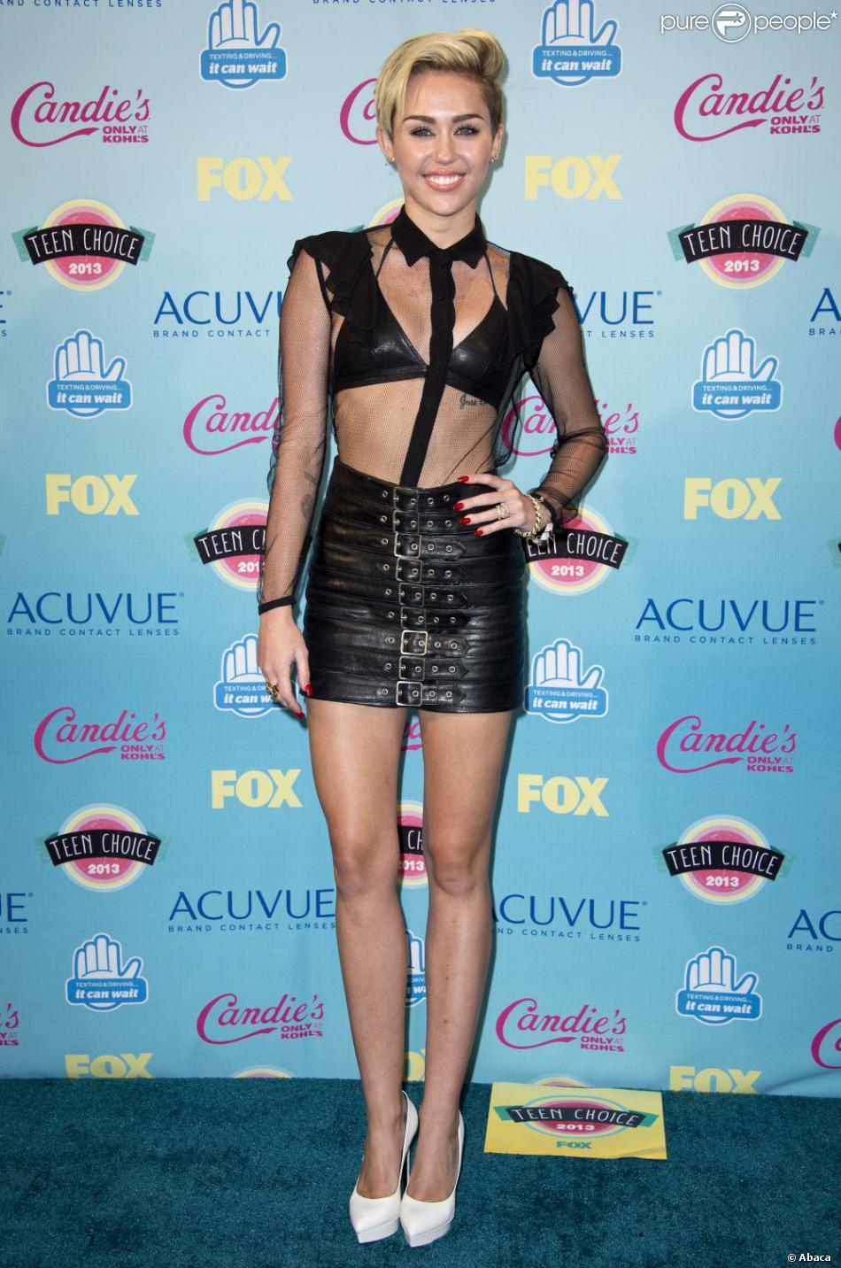 Miley Cyrus, tout de Saint Laurent vêtue avec un look de la collection automne-hiver 2013 et des souliers blancs, assiste aux Teen Choice Awards 2013 au Gibson Amphitheatre. Los Angeles, le 11 août 2013.