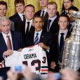 Barack Obama avec le maillot des Blackhawks de Chicago, équipe victorieuse de la Coupe Stanley en 2013, au milieu des joueurs et du staff, le 4 novembre 2013 à la Maison Blanche à Washington