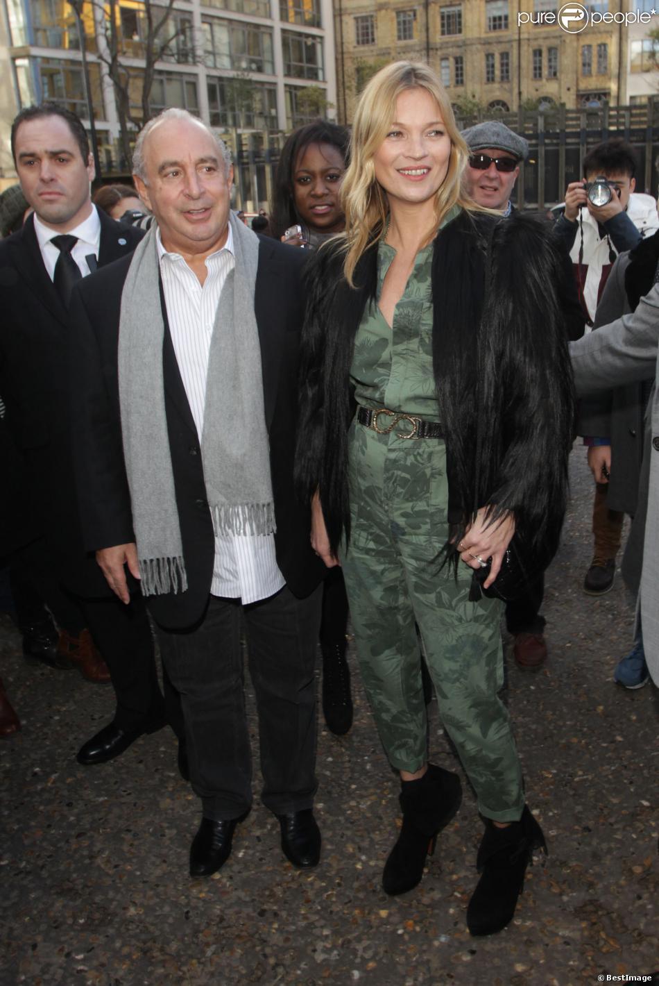 Kate Moss arrive au défilé Topshop Unique avec Sir Philip Green, habillée d'une veste en fourrure, d'une combinaison Topshop et de bottines noires Azzedine Alaïa. Londres, le 16 février 2014.