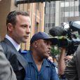 Oscar Pistorius escorté par la police à la sortie du tribunal de Pretoria, le 3 mars 2014
