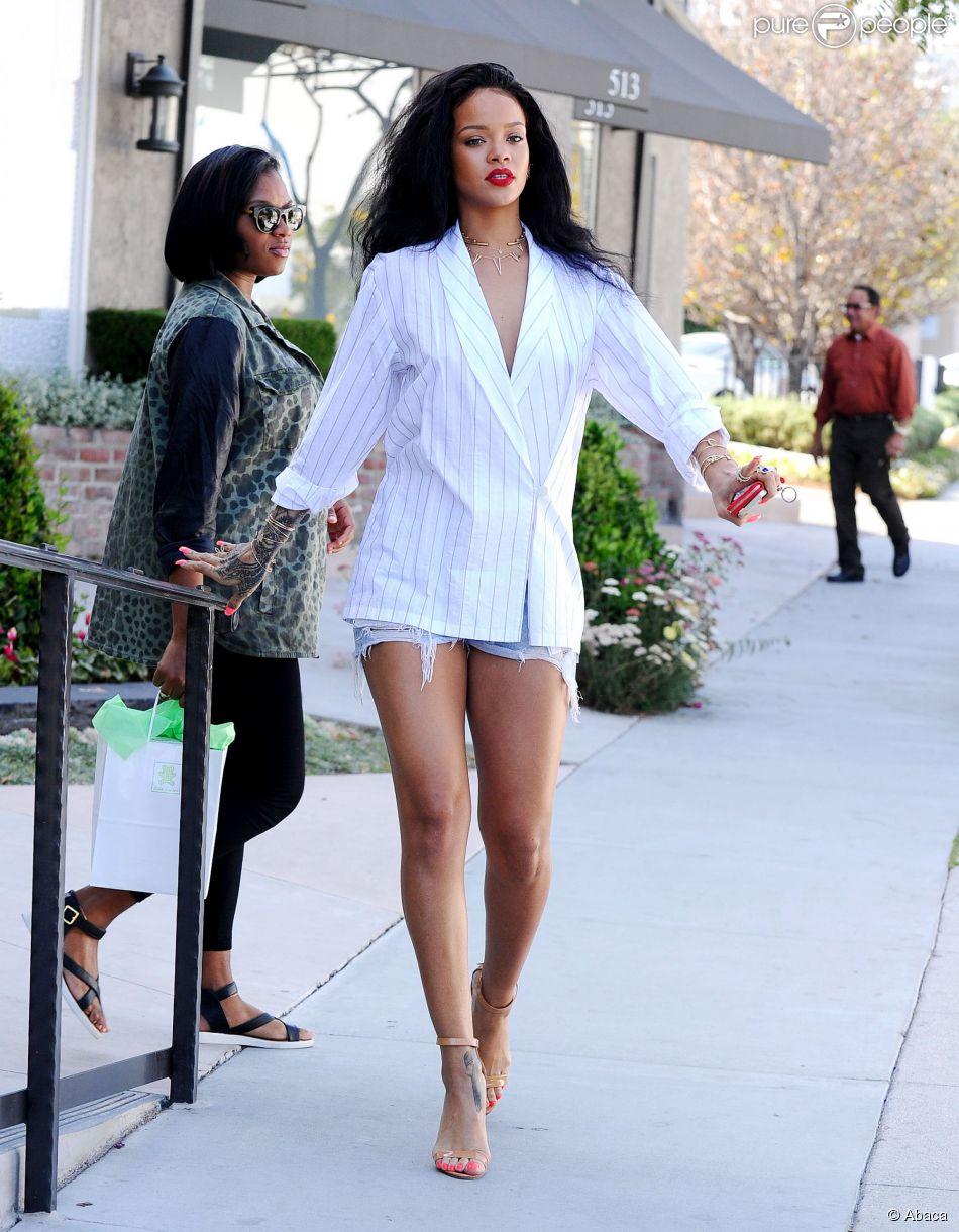 Rihanna en pleine séance shopping à Los Angeles, porte une veste blanche à rayures sans soutien-gorge, un mini-short en jean et des sandales Maolo Blahnik. Le 22 avril 2014.