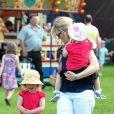 Autumn Phillips avec ses filles Isla, dans ses bras, et Savannah, qui fait un caprice, au Royal Windsor Horse Show le 17 mai 2014.