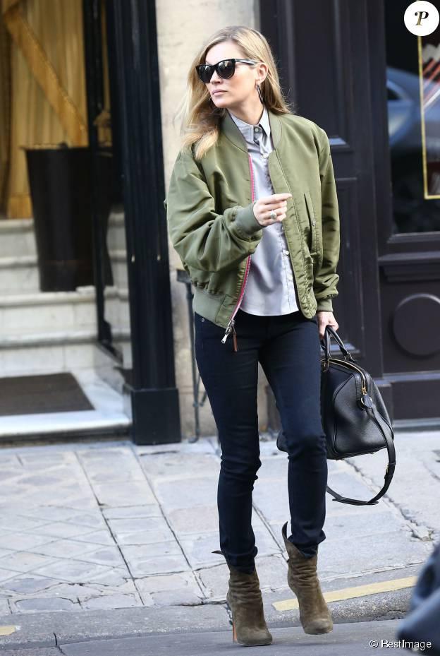 Kate Moss quitte l'hôtel Costes à Paris, habillée d'un bomber réversible kaki et rose, d'une chemise, d'un jean noir rag & bone et de bottines Alaïa. Des lunettes de soleil et un sac Saint Laurent accessoirisent sa tenue. Le 6 novembre 2014.