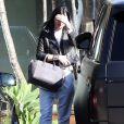 Kylie Jenner quitte le salon de coiffure Andy LeCompte à West Hollywood, habillée d'une veste en cuir noire, d'un ensemble blanc et de baskets Nike + R.T. (modèle Nike Air Force 1 revisité par Riccardo Tisci). Un sac gris Givenchy (modèle Antigona) complète sa tenue. Le 3 novembre 2014.