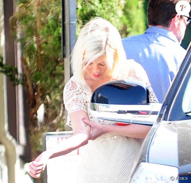 Tori Spelling observe sa blessure au bras à la sortie du restaurant japonais Benihana à Encino, le 5 avril 2015