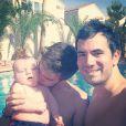 L'animateur Alex Goude, Romain et leur bébé Elliot posent ensemble dans la piscine. Juin 2015.