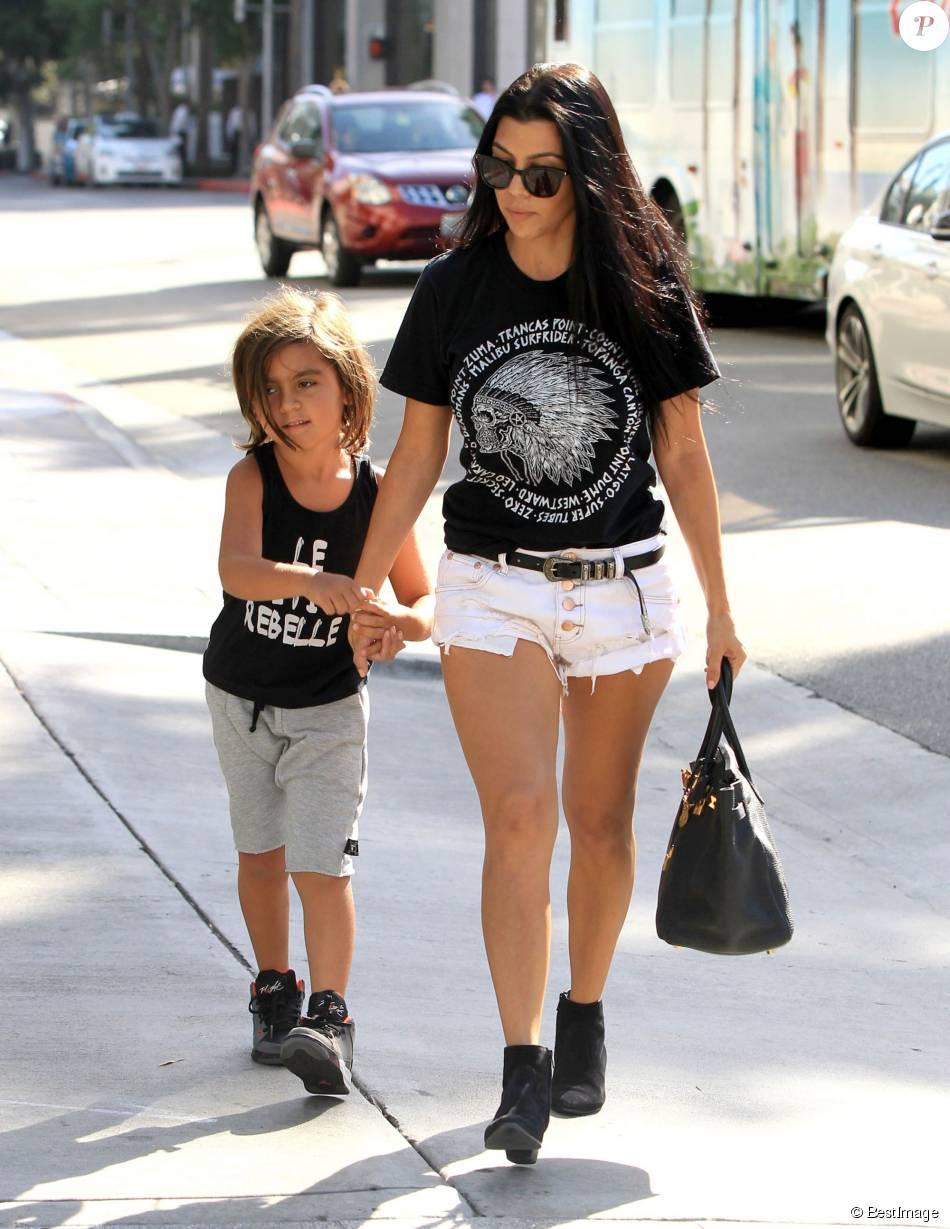 Kourtney Kardashian va faire du shopping avec son fils Mason à Beverly Hills, habillée d'un t-shirt noir, d'un mini-short blanc One Teaspoon et de bottines Saint Laurent. Des lunettes de soleil, une ceinture Saint Laurent et un sac Hermès (modèle Birkin) accessoirisent sa tenue. Le 3 août 2015.