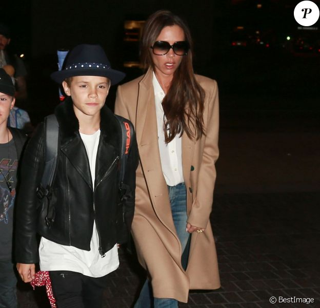 David, Victoria Beckham et leurs enfants arrivent à l'aéroport LAX de Los Angeles. Victoria porte un manteau (pré-collection automne-hiver 2015) et une chemise blanche Victoria Beckham, un jean R13 et des souliers au motif léopard. Le 31 octobre 2015.