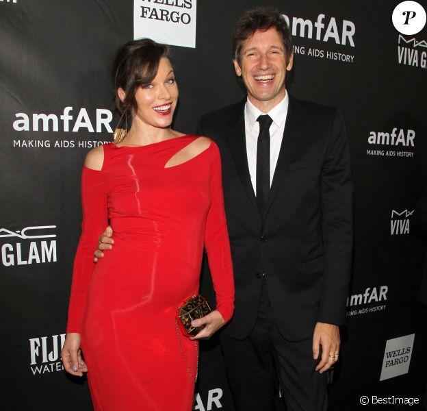 Milla Jovovich (enceinte) (robe Donna Karan) et son mari Paul W.S. Anderson - Soirée amFAR Inspirational gala à Los Angeles le 29 octobre 2014