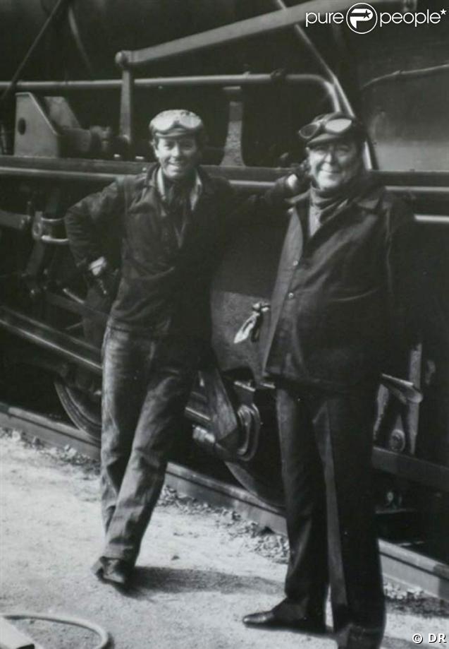 Guy Breton en tenue de mécanicien, au pied d'une locomotive, en compagnie de son ami Christian Morin