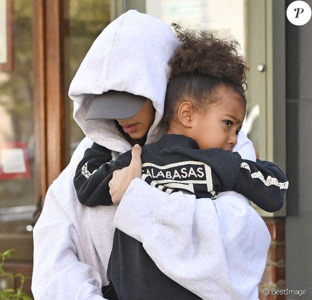 Kim Kardashian, cachée par ses vêtements, et sa fille North sortent de son appartement à New York, le 6 octobre 2016. Les photographes ne l'avaient pas vue depuis son retour précipité de Paris après son agression.